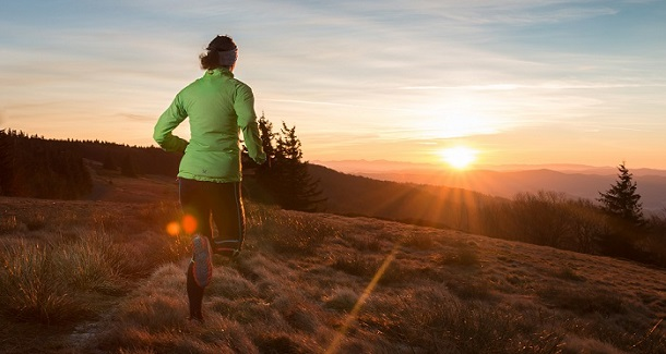young woman running on the trail in the cold spring mountain sunset